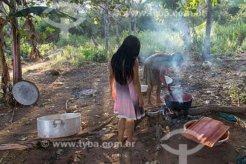 Mulher e jovem indígena cozinhando na aldeia Aiha da tribo Kalapalo - ACRÉSCIMO DE 100% SOBRE O VALOR DE TABELA  - Querência - Mato Grosso (MT) - Brasil
