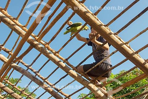 Menino Kalapalo brincando com papagaio durante trabalho de cobertura da oca com sapé na aldeia Aiha da tribo Kalapalo - ACRÉSCIMO DE 100% SOBRE O VALOR DE TABELA  - Querência - Mato Grosso (MT) - Brasil