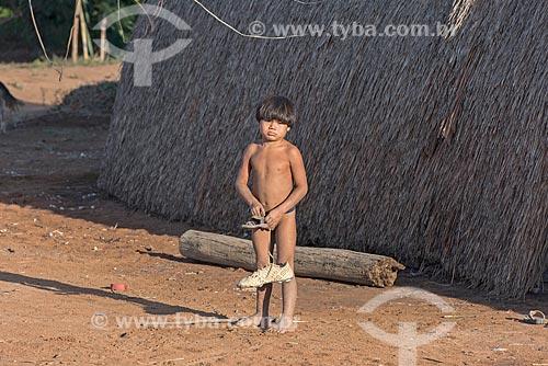 Menino indígena da aldeia Aiha da tribo Kalapalo brincando com chuteira - ACRÉSCIMO DE 100% SOBRE O VALOR DE TABELA  - Querência - Mato Grosso (MT) - Brasil