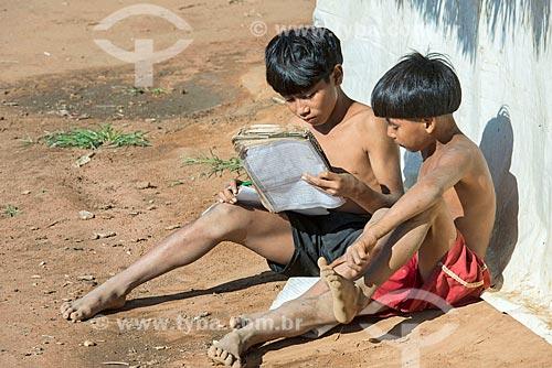 Meninos indígenas na aldeia Aiha da tribo Kalapalo interagindo com caderno escolar - ACRÉSCIMO DE 100% SOBRE O VALOR DE TABELA  - Querência - Mato Grosso (MT) - Brasil