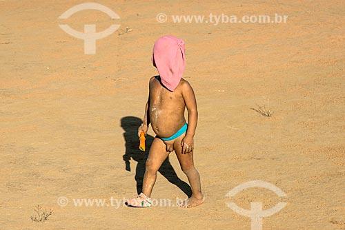 Menino indígena escondendo o rosto na aldeia Aiha da tribo Kalapalo - ACRÉSCIMO DE 100% SOBRE O VALOR DE TABELA  - Querência - Mato Grosso (MT) - Brasil