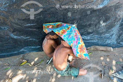 Meninos indígenas escondendo o rosto na aldeia Aiha da tribo Kalapalo - ACRÉSCIMO DE 100% SOBRE O VALOR DE TABELA  - Querência - Mato Grosso (MT) - Brasil