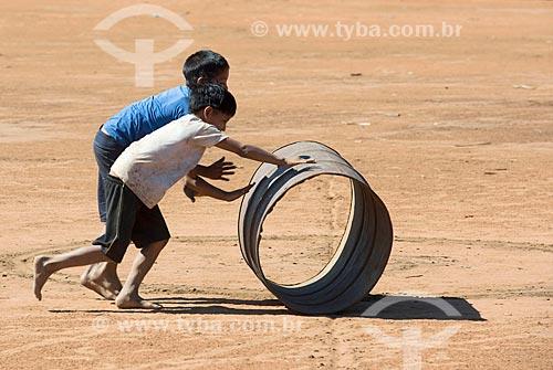 Meninos indígenas brincando com barril na aldeia Aiha da tribo Kalapalo - ACRÉSCIMO DE 100% SOBRE O VALOR DE TABELA  - Querência - Mato Grosso (MT) - Brasil