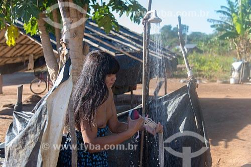Mulher indígena usando ducha plástica nos fundos de oca na aldeia Aiha da tribo Kalapalo - ACRÉSCIMO DE 100% SOBRE O VALOR DE TABELA  - Querência - Mato Grosso (MT) - Brasil