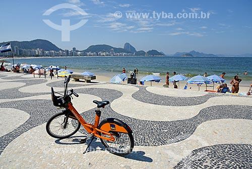 Bicicleta pública - para aluguel - no calçadão da Praia de Copacabana - Posto 6 - com o Pão de Açúcar ao fundo  - Rio de Janeiro - Rio de Janeiro (RJ) - Brasil