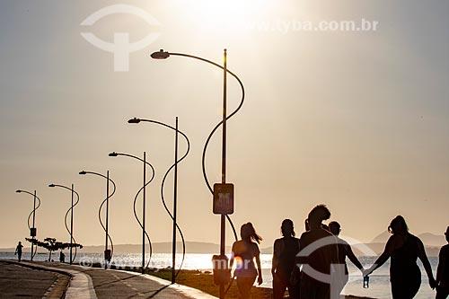 Pessoas caminhando na orla da Lagoa de Araçatiba durante o pôr do sol  - Maricá - Rio de Janeiro (RJ) - Brasil