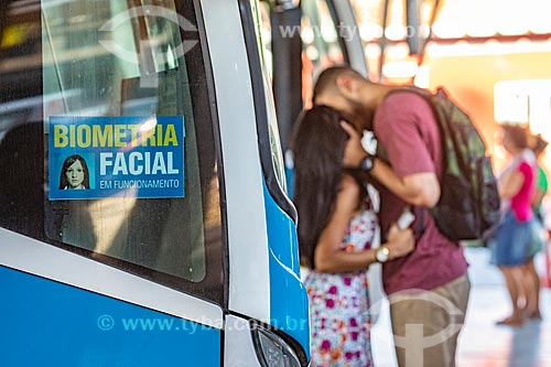 Adesivo informando a utilização de sistema de Biometria Facial em ônibus na Rodoviária do Povo de Maricá - antigo Terminal Rodoviário Jacinto Luis Caetano - com casal se beijando ao fundo  - Maricá - Rio de Janeiro (RJ) - Brasil