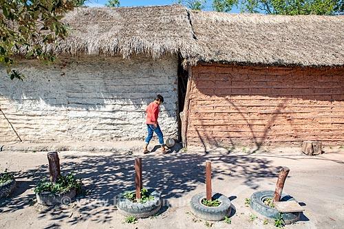 Menino indígena jogando futebol próximo à casa de pau-a-pique com cobertura de sapé na Aldeia Mata Verde Bonita (Tekoa Ka Aguy Ovy Porã) da Tribo Guarani  - Maricá - Rio de Janeiro (RJ) - Brasil