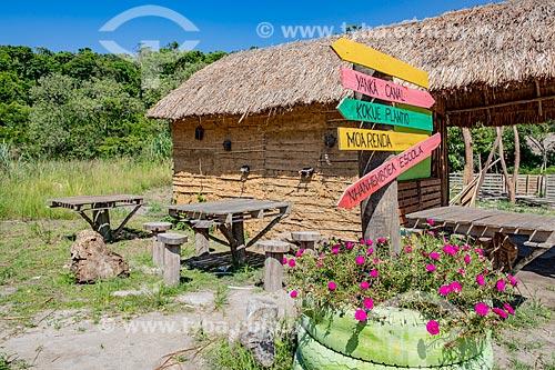 Mesas, casa de pau-a-pique com cobertura de sapé e placas de sinalização bilíngue na Aldeia Mata Verde Bonita (Tekoa Ka Aguy Ovy Porã) da Tribo Guarani  - Maricá - Rio de Janeiro (RJ) - Brasil