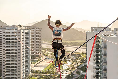 Praticante de slackline entre os prédios do Condomínio Residencial Ilha Pura Vila dos Atletas - edifícios onde os atletas se hospedaram durante os Jogos Olímpicos - Rio 2016 - durante o pôr do sol  - Rio de Janeiro - Rio de Janeiro (RJ) - Brasil