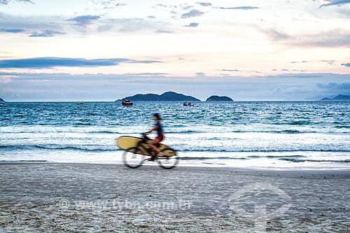 Surfista com prancha de surf em bicicleta na orla da Praia do Pântano do Sul  - Florianópolis - Santa Catarina (SC) - Brasil