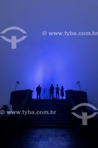 Fotógrafos no Cristo Redentor (1931) envolto em nuvens com iluminação especial - azul - devido à mobilização contra o câncer de próstata  - Rio de Janeiro - Rio de Janeiro (RJ) - Brasil