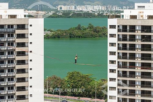 Praticante de slackline entre os prédios do Condomínio Residencial Ilha Pura Vila dos Atletas com a Lagoa de Jacarepaguá ao fundo  - Rio de Janeiro - Rio de Janeiro (RJ) - Brasil
