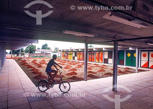 Criança andando de bicicleta em escola durante a construção de Brasília com pintura a esmalte sobre madeira e vidro de Athos Bulcão em portas  - Brasília - Distrito Federal (DF) - Brasil