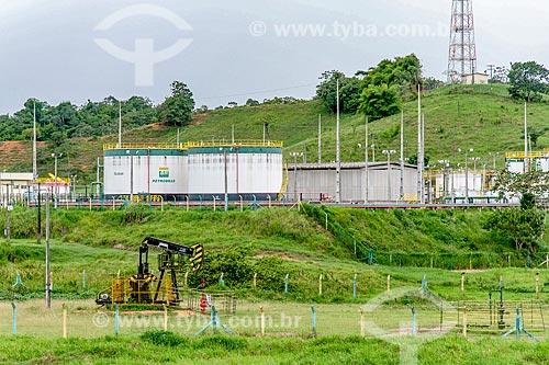 Bomba de vareta de sucção - também conhecida como Cavalo de pau - extraindo petróleo no perímetro urbano da cidade de Riachuelo com tanques ao fundo  - Riachuelo - Sergipe (SE) - Brasil