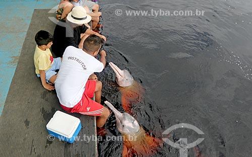 Turistas observando boto-cor-de-rosa (Inia geoffrensis) - flutuante dos botos no Rio Negro  - Novo Airão - Amazonas (AM) - Brasil