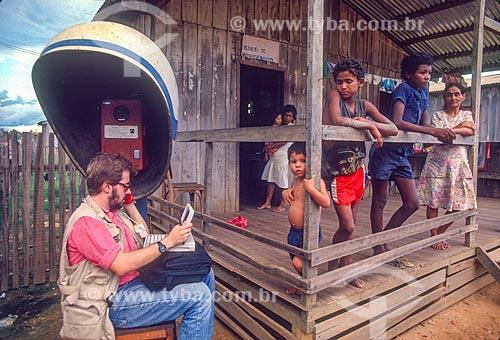 Homem utilizando telefone público e laptop próximo à casa simples - década de 90  - Xapuri - Acre (AC) - Brasil