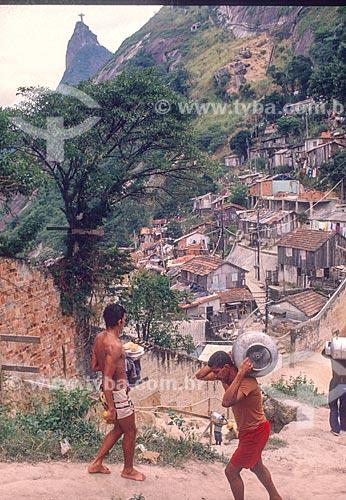 Morador carregando botijão de gás na favela Santa Marta com o Cristo Redentor ao fundo - década de 90  - Rio de Janeiro - Rio de Janeiro (RJ) - Brasil