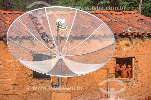 Detalhe de antena parabólica com casa de pau-a-pique ao fundo - década de 2000  - Mossoró - Rio Grande do Norte (RN) - Brasil