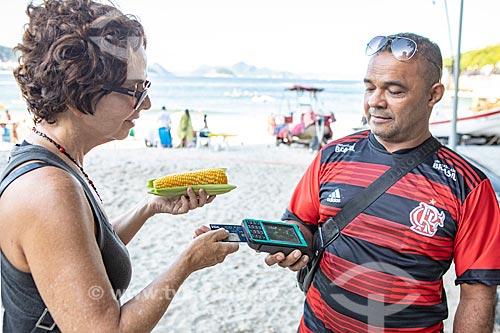 Vendedor ambulante de milho cozido usando máquina de cartão na orla da Praia de Copacabana  - Rio de Janeiro - Rio de Janeiro (RJ) - Brasil