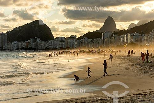 Banhistas na Praia do Leme durante o pôr do sol com o Morro dos Cabritos e o Morro Dois Irmãos ao fundo  - Rio de Janeiro - Rio de Janeiro (RJ) - Brasil