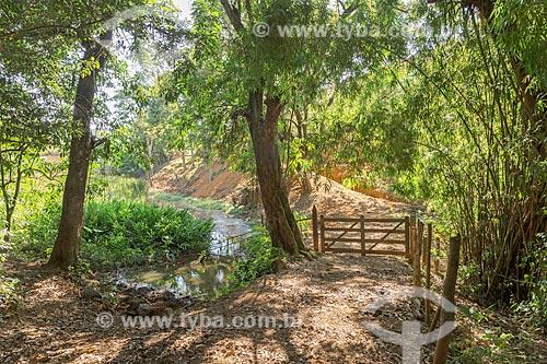 Córrego e porteira em estrada de terra na zona rural da cidade de Guarani  - Guarani - Minas Gerais (MG) - Brasil