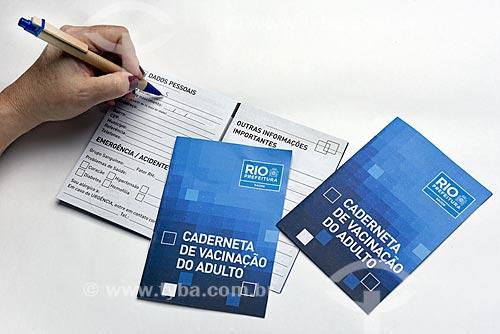 Pessoa preenchendo com dados pessoais a Caderneta de Vacinação do Adulto fornecida gratuitamente no Centro Municipal de Saúde  - Rio de Janeiro - Rio de Janeiro (RJ) - Brasil
