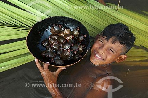 Detalhe de menino mergulhando no Rio Negro com tartarugas Irapuca (Podocnemis erythrocephala) na Reserva de Desenvolvimento Sustentável Puranga Conquista  - Manaus - Amazonas (AM) - Brasil