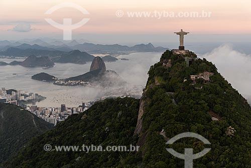 Foto aérea do Cristo Redentor com o Pão de Açúcar ao fundo durante o pôr do sol com nevoeiro  - Rio de Janeiro - Rio de Janeiro (RJ) - Brasil