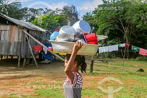 Jovem ribeirinha carregando panelas na Reserva de Desenvolvimento Sustentável Anamã  - Barcelos - Amazonas (AM) - Brasil