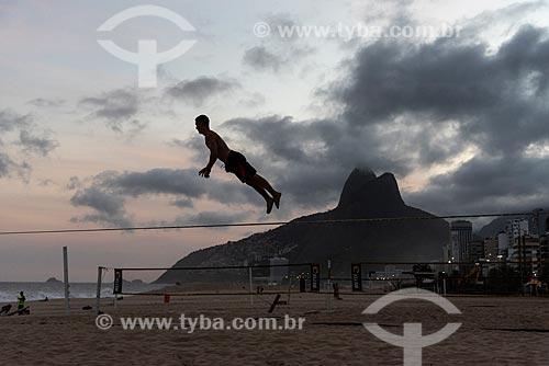 Praticante de slackline na Praia de Ipanema durante o pôr do sol com o Morro Dois Irmãos ao fundo  - Rio de Janeiro - Rio de Janeiro (RJ) - Brasil