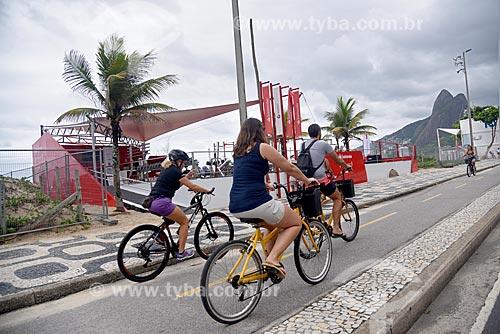 Ciclistas em ciclovia na orla da Praia de Ipanema com o Morro Dois Irmãos ao fundo  - Rio de Janeiro - Rio de Janeiro (RJ) - Brasil