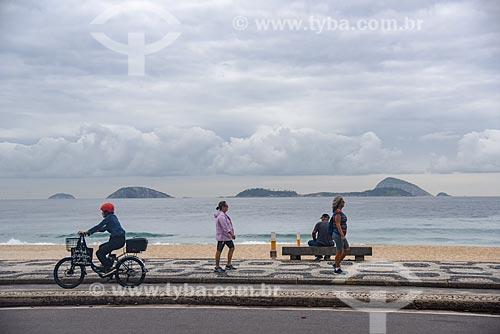 Ciclista e pedestres em ciclovia na orla da Praia do Leblon com o Monumento Natural das Ilhas Cagarras ao fundo  - Rio de Janeiro - Rio de Janeiro (RJ) - Brasil
