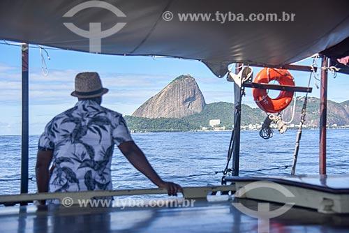 Homem observando a vista durante passeio turístico de barco na Baía de Guanabara com o Pão de Açúcar ao fundo  - Rio de Janeiro - Rio de Janeiro (RJ) - Brasil