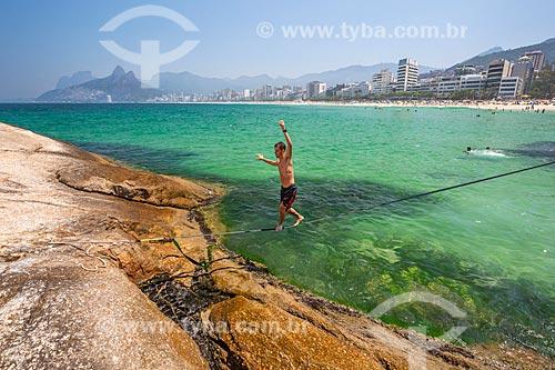 Praticante de slackline na Praia do Arpoador com o Morro Dois Irmãos e a Pedra da Gávea ao fundo  - Rio de Janeiro - Rio de Janeiro (RJ) - Brasil