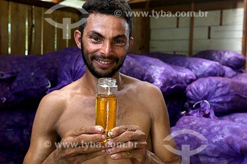 Ribeirinho segurando óleo de andiroba (Carapa guianensis) - conhecida por suas propriedades cosméticas - na Comunidade Ribeirinha do Bauana  - Carauari - Amazonas (AM) - Brasil