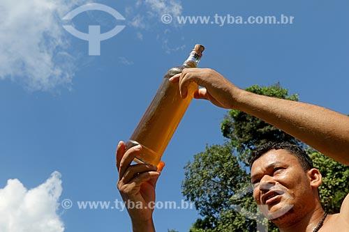 Produtor rural segurando óleo de andiroba (Carapa guianensis) - conhecida por suas propriedades cosméticas - na Comunidade Ribeirinha do Bauana  - Carauari - Amazonas (AM) - Brasil