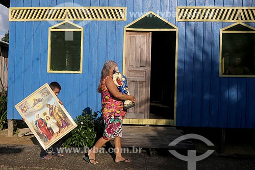 Mulher carregando estátua de São Pedro e menino carregando quadro da Sagrada Família na Comunidade Ribeirinha do Bom Jesus  - Carauari - Amazonas (AM) - Brasil