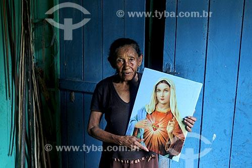 Produtora rural da comunidade ribeirinha do Bauana na Reserva Extrativista do Médio Juruá segurando quadro do Sagrado Coração de Maria  - Carauari - Amazonas (AM) - Brasil