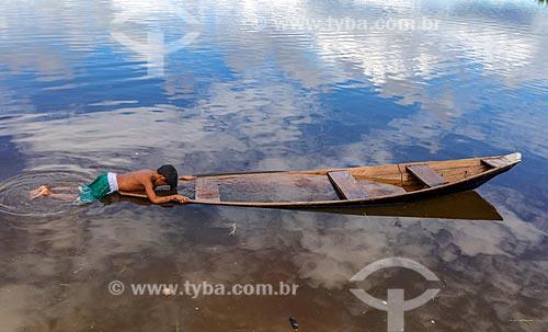 Menino da comunidade ribeirinha na Reserva de Desenvolvimento Sustentável Puranga Conquista brincando em canoa no Rio Negro  - Manaus - Amazonas (AM) - Brasil