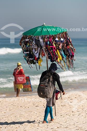 Vendedor ambulante de biquíni e sorveteiro ao fundo na Praia da Barra da Tijuca  - Rio de Janeiro - Rio de Janeiro (RJ) - Brasil