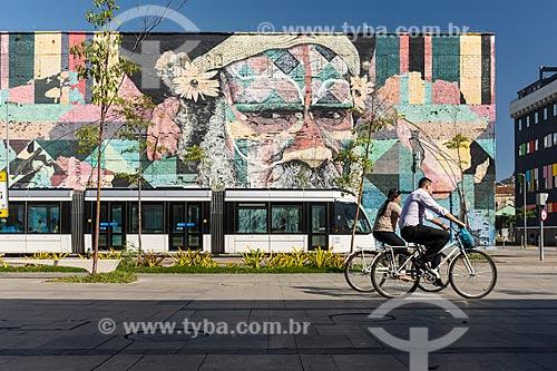 Veículo leve sobre trilhos e casal andando de bicicleta na Orla Prefeito Luiz Paulo Conde com o Mural Etnias ao fundo  - Rio de Janeiro - Rio de Janeiro (RJ) - Brasil