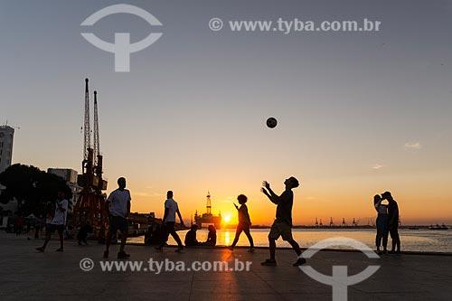Jovens jogando futebol (altinha) na Praça Mauá com plataforma de petróleo ao fundo durante o pôr do sol  - Rio de Janeiro - Rio de Janeiro (RJ) - Brasil