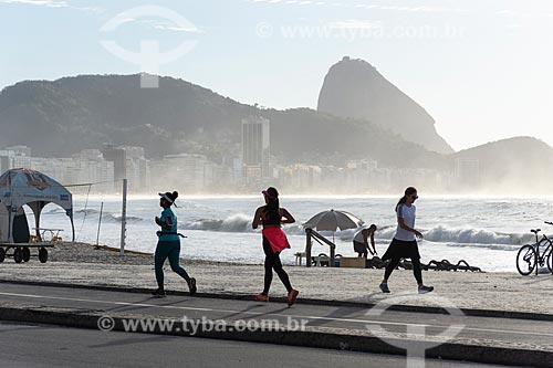 Mulheres correndo no calçadão da Praia de Copacabana com o Pão de Açúcar ao fundo  - Rio de Janeiro - Rio de Janeiro (RJ) - Brasil
