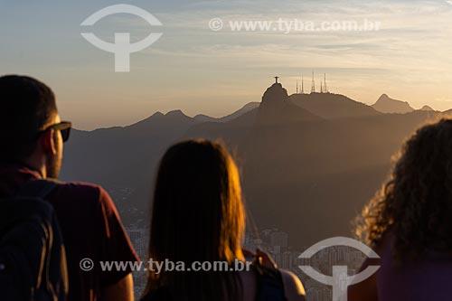 Pessoas observando o pôr do sol a partir do mirante do Pão de Açúcar com o Cristo Redentor ao fundo  - Rio de Janeiro - Rio de Janeiro (RJ) - Brasil