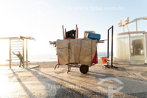 Detalhe de carrinho de burro-sem-rabo com cadeiras de praia na orla da Praia de Copacabana durante o amanhecer  - Rio de Janeiro - Rio de Janeiro (RJ) - Brasil