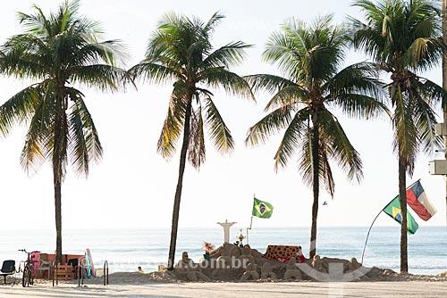 Escultura em areia de mulheres de biquíni e Cristo Redentor com a bandeira do Brasil na Praia de Copacabana