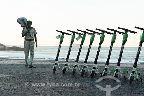 Patinete elétrico para aluguel da Grin no calçadão da Praia do Arpoador com a estátua do maestro Tom Jobim ao fundo  - Rio de Janeiro - Rio de Janeiro (RJ) - Brasil
