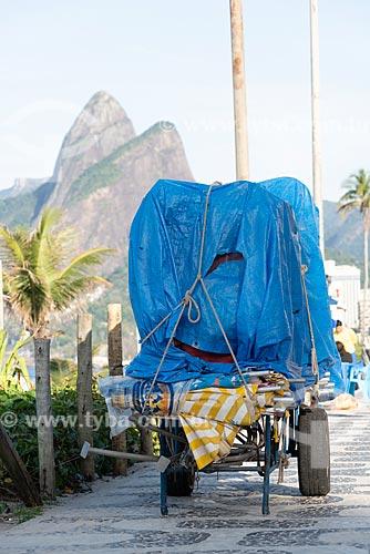 Detalhe de carrinho de burro-sem-rabo com cadeiras de praia na orla da Praia de Ipanema com o Morro Dois Irmãos  - Rio de Janeiro - Rio de Janeiro (RJ) - Brasil