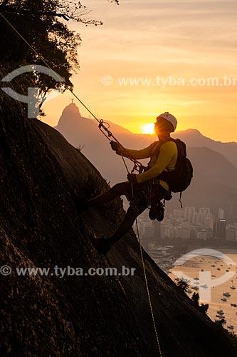 Alpinista durante a escalada no Morro da Urca durante o pôr do sol com o Cristo Redentor ao fundo  - Rio de Janeiro - Rio de Janeiro (RJ) - Brasil
